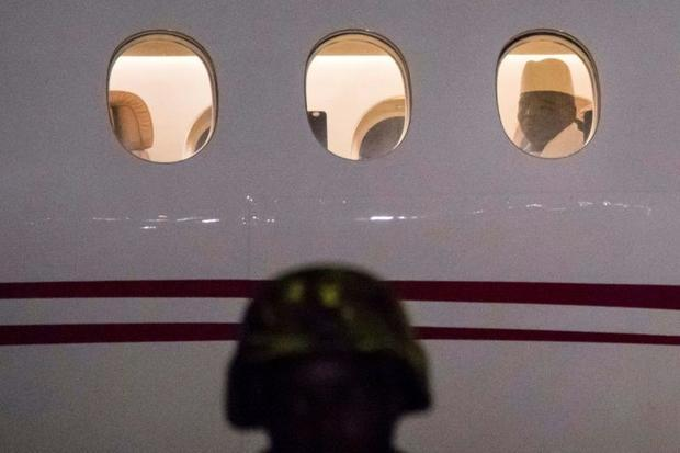 Out: Jammeh looks through a plane window as he leaves The Gambia on 21 January 2017