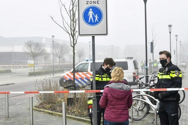Police officers speak with a pedestrian as they close off a street after an explosion occurred near ...