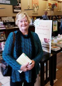 At a Barnes and Noble book signing  travel author Carole Bumpus holds her first novel  A Cup of Rede...
