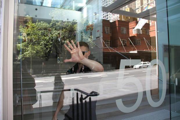 A security guard tries to stop photos being taken at the Sydney offices of 2Day FM at 50 Goulburn St...