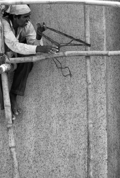 Worker ties bamboo poles together.