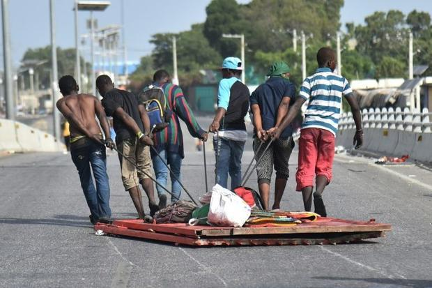 Looters carry away items during protests as calls escalate for President Jovenel Moise's resign...