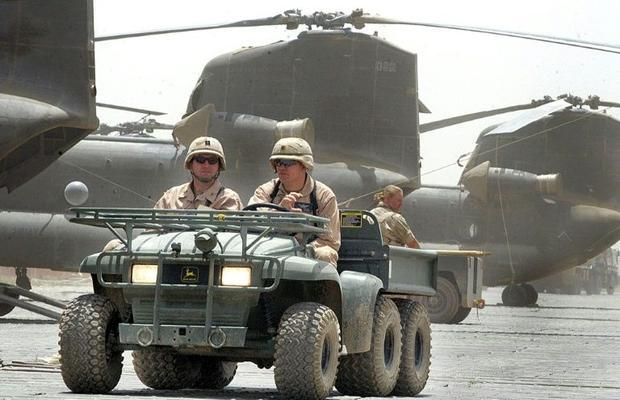 US soldiers drive past Chinook helicopters in 2002  a year after the invasion of Afghanistan at Bagr...