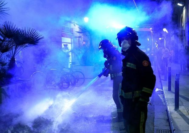 Firefighters put out a fire after a demonstration against a curfew in Barcelona as virus cases spike...
