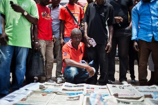 People gather in Brazzaville around a vendor selling copies of Congolese daily newspapers on March 2...