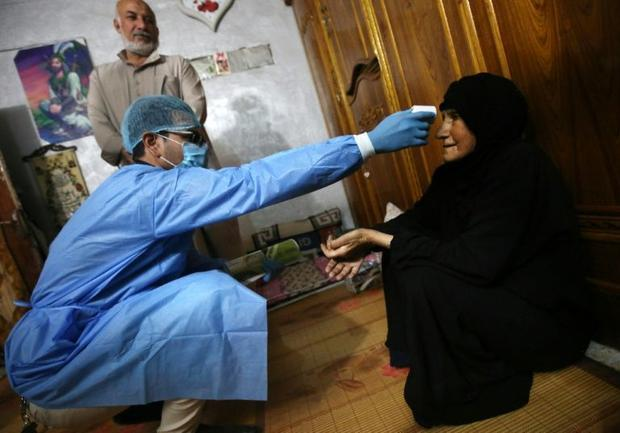 An Iraqi public hospital doctor checks a woman's temperature for COVID-19 in the capital Baghda...