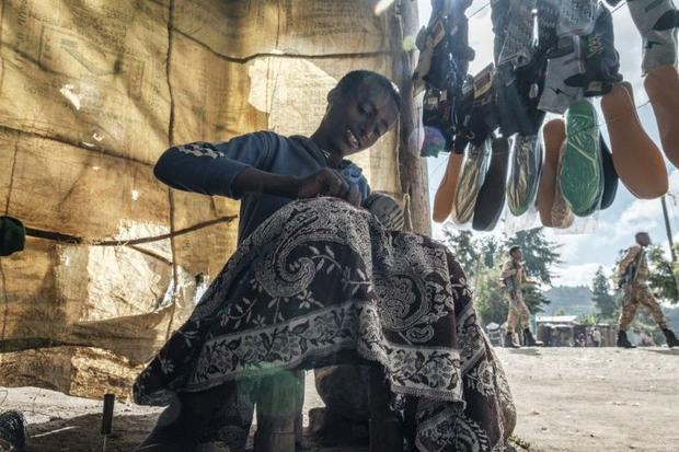 A cobbler in Korem  a town north of Alamata  repairs a shoe as soldiers of the Amhara special forces...