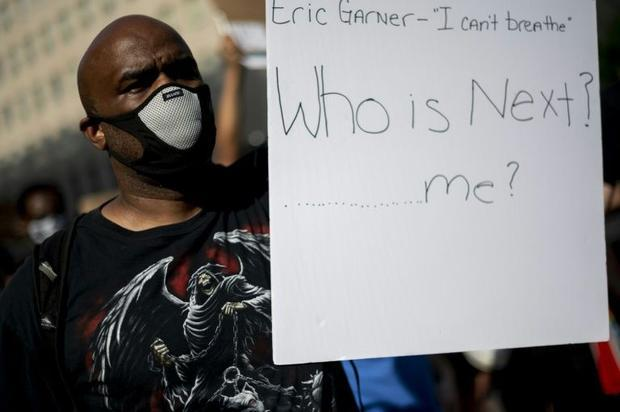 A protestor holds a sign near the White House in Washington  DC  on June 2  2020. Experts have also ...