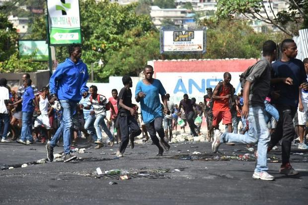 Residents and looters flee when Haitian police arrive in Delmas  a commune near Port-au-Prince  Hait...