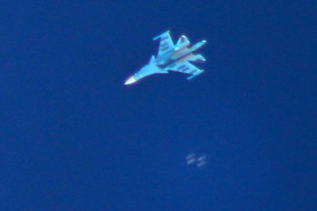 A picture taken on September 7  2018 shows a Russian Sukhoi Su-34 fighter jet dropping bombs over th...