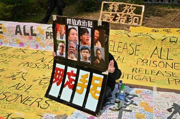 A supporter displays a placard outside the West Kowloon court in Hong Kong ahead of  appearances by ...