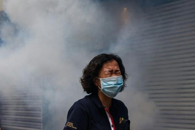 A Hong Kong woman shown after riot police fired tear gas to disperse protesters taking part in a pro...