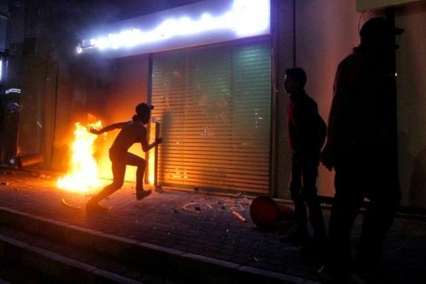 A protester kicks the entrance of a bank in Sidon