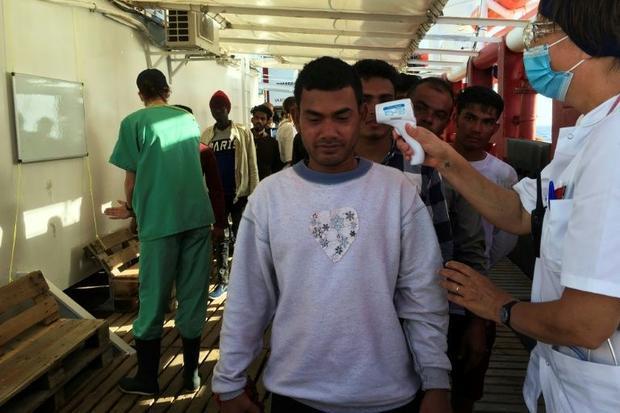 A medic of SOS Mediterranee takes the temperature of rescued migrants