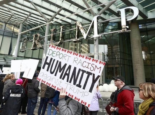 Protestors gather outside at the front of the Trump International Tower & Hotel during the offic...