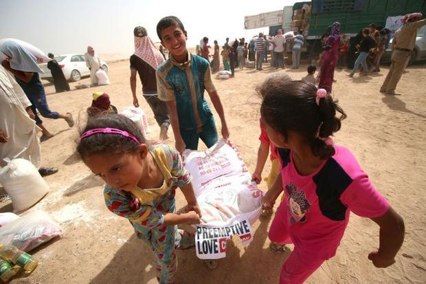 Children carry bags of donated food at a camp for displaced Iraqis in Khaldiyeh on June 20  2016