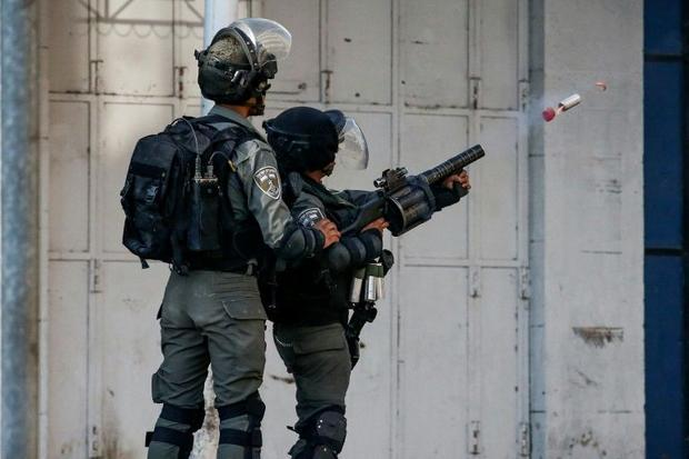 An Israeli border guard fires a tear gas canister amidst clashes with Palestinian demonstrators in t...
