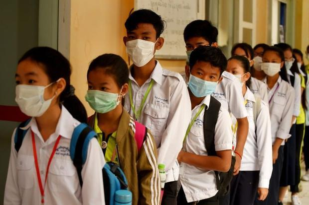Masked Cambodian students line up to disinfect their hands with an alcohol solution before entering ...
