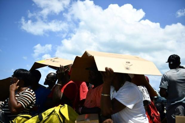 People seek shelter from the sun as they await evacuation at a dock in Marsh Harbour  Bahamas  on Se...