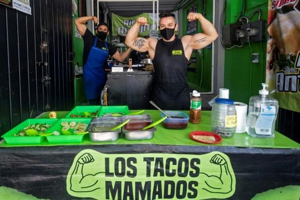 Mexican Ulises Perez  36  and Gustavo Contreras  30  pose as they work at a taco restaurant set up a...