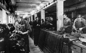 Jewish slave workers in striped uniforms work in a Nazi ammunition factory near Dachau concentration...