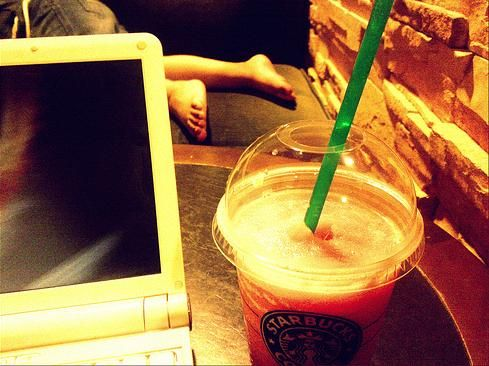 Photo of starbucks drink next to a netbook with a little girl s legs in the background